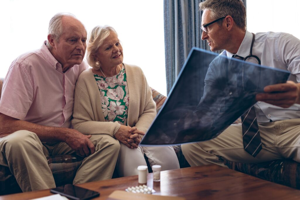 Male doctor discussing over x ray with senior couple at retirement home